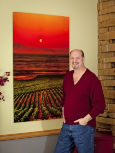 Richard Duval, Seattle-area wine photographer, in front of an image on metal of Sagemoor Vineyards in Pasco of a harvest moon in the dawn sky. Courtesy of Richard Duval.
