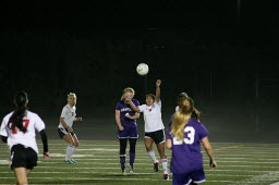 Anyssa DeVera rises up for the soccer during a misty Wednesday night, at Doc Harris Stadium. Camas beat Wenatchee 4-0 in the first round of the state tournament. (Camas Washougal Post-Record)